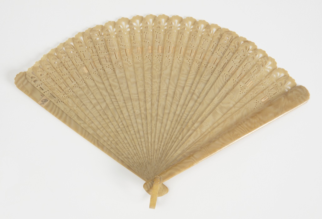 Brisé fan with pierced sticks. Moire effect produced by darker brown color swirling through tan color.