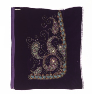 Amethyst velvet with scrolls embroidered in gold thread ornamented with colored beads set in scrolling paisley shapes. Partly bordered by a band made up of ribbon and bead ornaments.