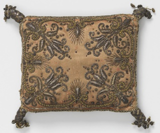 Small rectangular cushion of deep rose satin embroidered in flat gold, gold thread and sequins. Tassels of metallic thread at the corners. Conventionalized floral motifs at corners.