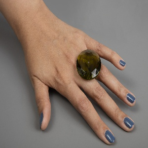 "Finger ring consisting of large, faceted, circular green glass ""gem"" on inverted T-shaped silver base to be secured between fingers."