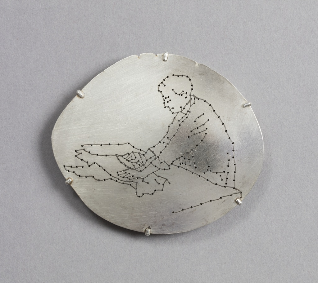 Vaguely oval silver brooch, the surface decorated with embroidery of a figure at work.