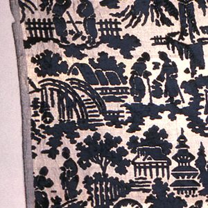 Sheer gold ground fabric with black pile in a chinoiserie design of figures in traditional dress in a landscape of homes, bridges and trees as well as temples and pagodas.