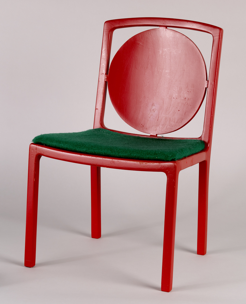 Red chair with straight legs; back filled with a large disk supported by square frame. Seat, lightly cushioned, upholstered in green.