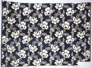 Allover design of stylized roses in gold on a black ground.