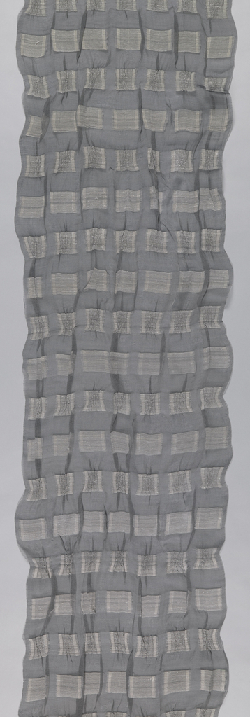 Sheer grey panel with white bands of supplementary weft that is cut to make a pattern of squares and rectangles across the surface. Alternating bands of supplementary weft were shrunk before cutting to create creases in the grey textile.