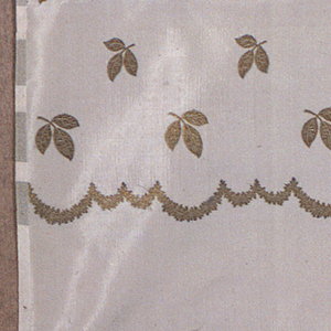 Off-white taffeta fabric with a border design of a scalloped line and leaves in metallic gold thread. There are four rows of leaves that are graduated in size with the largest leaves closet to the scalloped line.