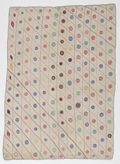 Quilt of cotton, embroidered in cotton in diagonally striped pattern, forming compartments filled with stylized circular motifs in blue, red, yellow, and green.