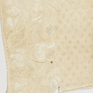 One half of a sleeveless bodice front of off-white linen solidly decorated in elaborate floral and lattic patterns in quilting, drawn work and embroidery in white linen thread.