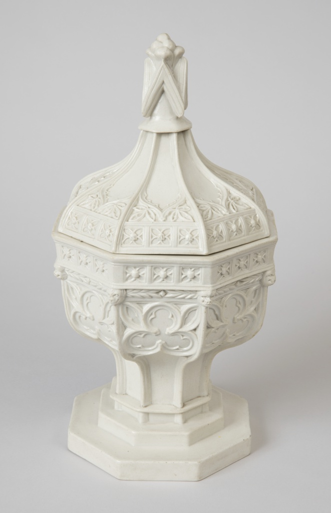 Font with cover of gothic arches formed from radiating cyma curves which result in a peaked dome shape. Segments of the dome are adorned with foliate patterns. The font is further decorated with tresfoils around the body of the basin and quatrefoils at the lip of both the basin and the lid. The font rises on a stepped plinth and an octagonal base.