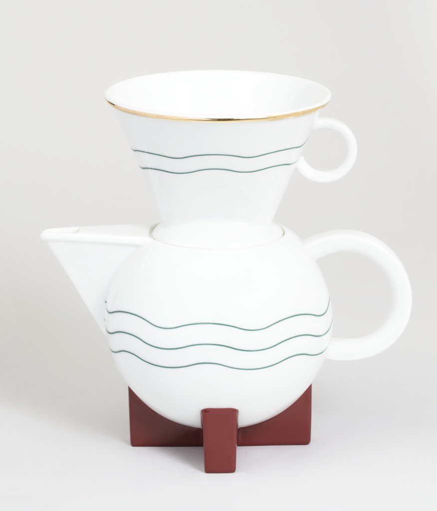Globular white body with triangular spout and circular handle, decorated by two wavy blue-green lines and integral x-shaped base in red-brown glaze.
