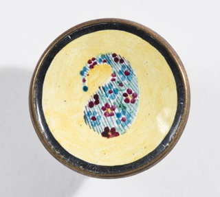 Concave button painted in design of Persian cone motive (red and blue) on yellow ground with black border; copper shank. On card 10.