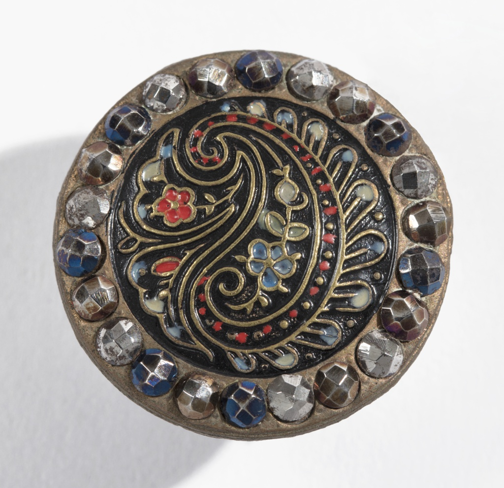(a) Brass button with design resembling Persian Cone stamped and painted in color, surrounded by facetted boses of cut steel in various colors; brass shank.  (b) Similar button in smaller size. Component -b is on card 42.