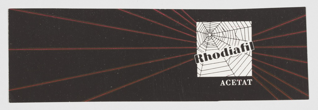 """Advertisement proof for Rhodiafil, a company that appears to specialize in acetate fabric. Contains a white box at right containing a spider's web, with """"Rhodiafil"""" printed across in black. """"ACETAT"""" is printed below in white. Background is black, with diagonal red lines emerging in a web-like fashion from the box."""