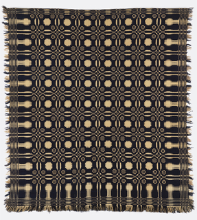 "Reversible coverlet in dark blue, off-white and light brown in a ""single snowball"" pattern with double intersecting circles and a pine tree border. Woven in two pieces and stitched together in the center. Fringe along both sides and bottom edge. Top edge is folded over and stitched."