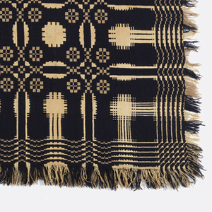 """Reversible coverlet in dark blue, off-white and light brown in a """"single snowball"""" pattern with double intersecting circles and a pine tree border. Woven in two pieces and stitched together in the center. Fringe along both sides and bottom edge. Top edge is folded over and stitched."""