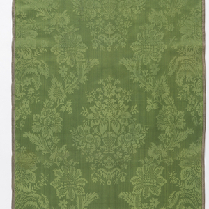 Green damask with a pattern of flowers and foliage in a vase framed by a running floral vine.