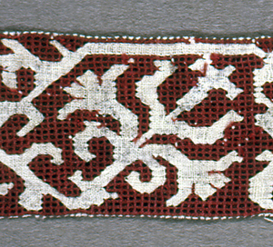 Pattern of diagonal floral sprays reserved in white on red background.