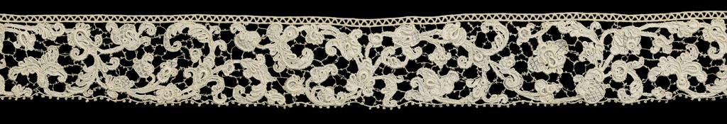 Border of Point de Venise à Rose with floral sprays running in a serpentine design. Pattern connected by picoted bars; outlined by cordonnet. Solidly-worked areas are interspersed with decorative filling stitches known as gaze quadrillée.