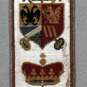 Narrow trimming band with a repeat of a heraldic shield surmounted by a crown in multi-color uncut pile on a white satin ground.