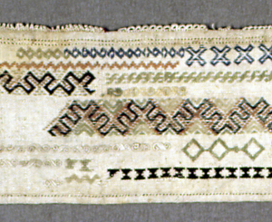 Long horizontal sampler divided into three columns, with bands of simple geometric patterns. Needlemade edging at the top.