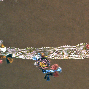 Lace band with floss flowers sewn at intervals. Loosely worked undyed silk bobbin lace with a scalloped edge dotted with single flowers and a few small knotted tassels of polychrome silk floss sewn at regular intervals.