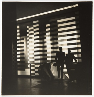 Black and white square photograph showing two figures standing on escalator to right of Joseph Albers mural in Pan Am building in high contrast.