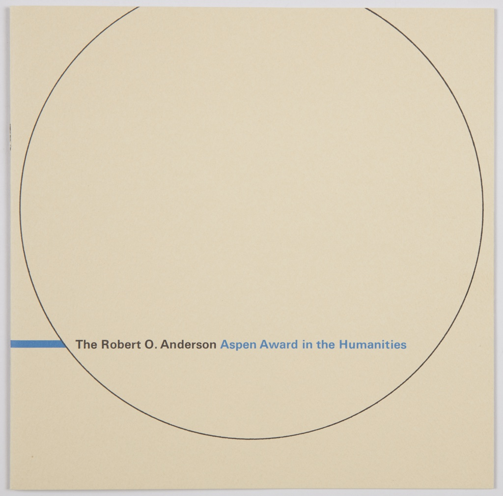 The Robert O. Anderson Aspen Award in the Humanities booklet. Cover consists of a circle, thinly outlined in black and cropped at the top on a light brown background. Printed in black and blue, lower portion of circle: The Robert O. Anderson [black] Aspen Award in the Humanities [blue]. A blue horizontal line appears on the left of the circle. Verso: Horizontal blue line along the lower portion, with a grey Aspen leaf above at left. Interior has white pages with black printed text and blue horizontal and vertical lines, as well as vellum pages containing images in brown. White form and envelope, with blue printed text, tucked inside.