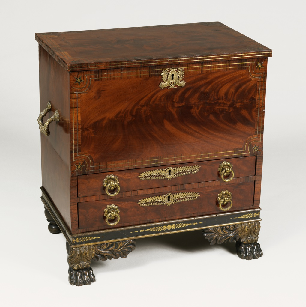Upright, rectangular form; veneered surface with two drawers surmounted by a drop front panel with inlay of light wood bands around edges, stars at corners and gilt bronze escutcheon in form of trophy; drawers with gilt bronze circular pulls and lily-of-the-valley escutcheons; rectangular gilt bronze handles on left and right side; two paw feet with gilt foliate decoration in front; turned rear feet.