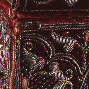 Rectangular box, probably a missal case, of red velvet embroidered in gold in high relief in a strap work pattern with stylized floral motifs. One side is hinged and fastened with small silver hooks. Silver eyelets on the end for cord handles.