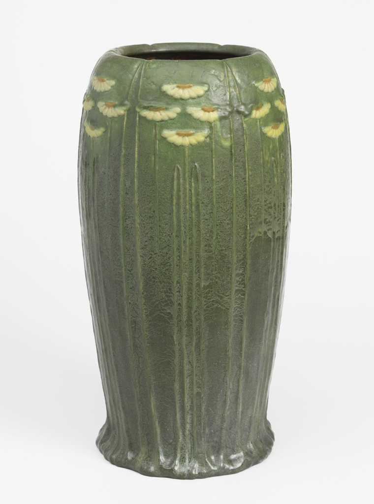 Buff-colored clay body, thrown. Elongated ovoid with slightly flaring free-formed base, incurving rim off shoulder. Modeled in low relief with attenuated pointed leaves, and around shoulder six group of four daisies each. Daisies in yellow and ochre; body is dark green with silvery veining overall. Foot rim with green mat glaze; rest of bottom white opaque high glaze. Interior in ochre high glaze.