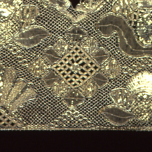Wide border of metallic lace in bold design of large diamond shapes alternating with large floral forms. Outer edge is scalloped.