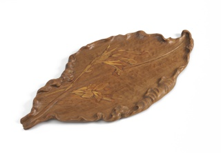 Carved leaf form with inlaid decoration of iris flowers on leafy stems.