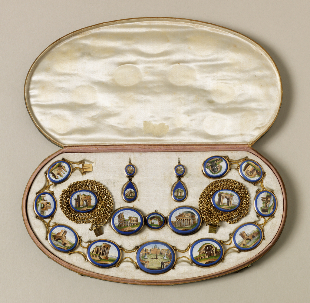Suite of jewelry with gold filigree mounts around micromosaic oval scenes of Rome in cobalt blue borders; comprising a necklace centered by a view of St Peter's, with various ruins, and the Colisseum, and Pantheon; a pair of gold bracelets each with one arch view, a pair of earrings, and a pair of brooches.