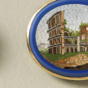 A gold oval brooch outlined in blue with an inner image of the Pantheon in Rome. Brooch is part of a set.