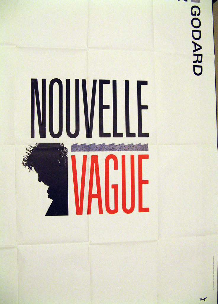 "On a white field, the word ""Nouvelle"", in black above ""Vague"", in red, separated by schematic blue wave, with black profile silhouette of man with ruffled hair, looking down. Upper right corner, the text ""Jean-Luc Godard."""