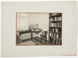 Photograph showing the interior of a study, featuring a chair at center, bookshelf on the right, and a desk underneath a window at left.