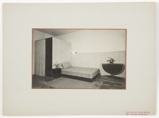 Photograph of a bedroom interior, featuring a side view of a bed at center. A rectangular rug and small table with a vase of flowers are positioned to the right of the bed, and a larger table, also containing a vase of flowers, is at the foot of the bed, at the right of the composition. A smaller room or area is behind the bed, covered with a curtain in front.