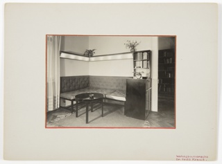 Photograph of a living room interior featuring an L-shaped couch at center facing the viewer. A rug and an oval-shaped table with a bowl on top are positioned in front of the couch. At right, a piece of furniture with a bookshelf above. Vases with flowers inside are positioned above the couch. A portion of a curtain is shown at left.