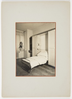 Photograph of an interior with wood floors featuring a fold-out bed with a duvet and pillows on top. A curtain-covered window and a tall plant on top of a ledge above a radiator appear in the background.
