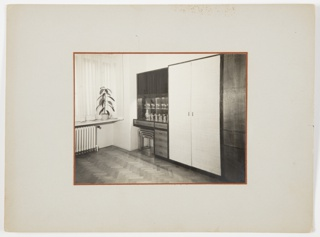 Photograph of an interior with wood floors featuring a large white closet at right, next to a piece of furniture with drawers, space for stacked stools underneath, and multiple glasses for drinking on top. A ledge with a tall plant above a radiator and a curtain-covered window appear at left. Appears to be the bedroom featured in 7185.4.2019 before the bed is unveiled and folded out.