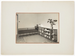 Photograph of an interior with wood floors featuring a long couch at left, with a rug in front. At right, a long, low piece of furniture with multiple shelves containing books and dishes; a tall plant sits on top.