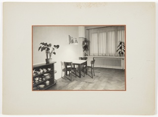 Photograph of an interior with wood floors featuring a square table at center surrounded by three wooden chairs. A rug is underneath the table, and a stretchable light is projected from the wall above. A long radiator appears at the back of the room underneath a ledge with a tall plant on top at right. A curtain covers the window above the ledge. At left foreground, a piece of furniture with a tall plant on top containing shelves filled with dishes appears.
