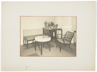 Photograph of an interior featuring a small couch or loveseat at left, a chair at right, and a square table in the center background covered with plants. At center foreground, a circular table, containing a bowl on top with fruit.