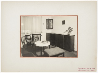 Photograph of an interior featuring a long piece of furniture containing drawers at right and a circular table, chair, and bench at left. A bowl of fruit sits on top of the circular table. A radiator and curtain-covered window appear in the background.