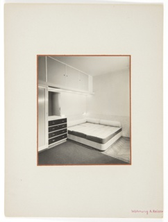 Photograph of a bedroom interior featuring a low bed with cylindrical pillows at center. A floor rug appears at the right of the bed, and a variety of drawers and storage space appear at left.