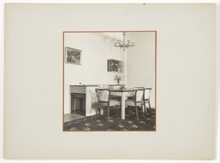 Photograph of a dining room interior featuring a table surrounded by four chairs at right, with a patterned rug underneath. A loveseat sits between two pieces of furniture at left behind the table. A chandelier is above the table, and the wall is covered with a painting and small shelf unit.