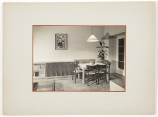 Photograph of an interior featuring a table surrounded by four chairs at right on top of a patterned rug. A bookshelf and long, low piece of furniture are at left, underneath a painting of flowers. A lamp hangs from the ceiling above the table.