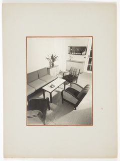 Photograph of an interior from above featuring a rectangular table at center, surrounded by a variety of chairs and a couch at left. A piece of furniture containing drawers, with a tall potted plant on top, appears next to the couch. A rectangular piece of furniture, with shelves above containing cups and pitchers, appears in the background.