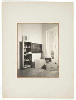 Photograph featuring the interior of a child's room. A bookshelf appears at left, a chalkboard appears at center, and wooden boxes appear at bottom right. A teddy bear is seen popping out of one of the boxes.