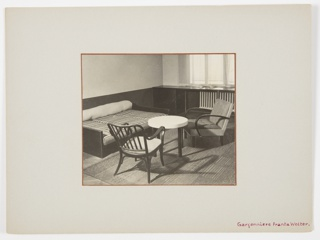 View of a corner bedroom/living room area in an apartment with daybed, two chairs, and a small table. Curtained windows at right.